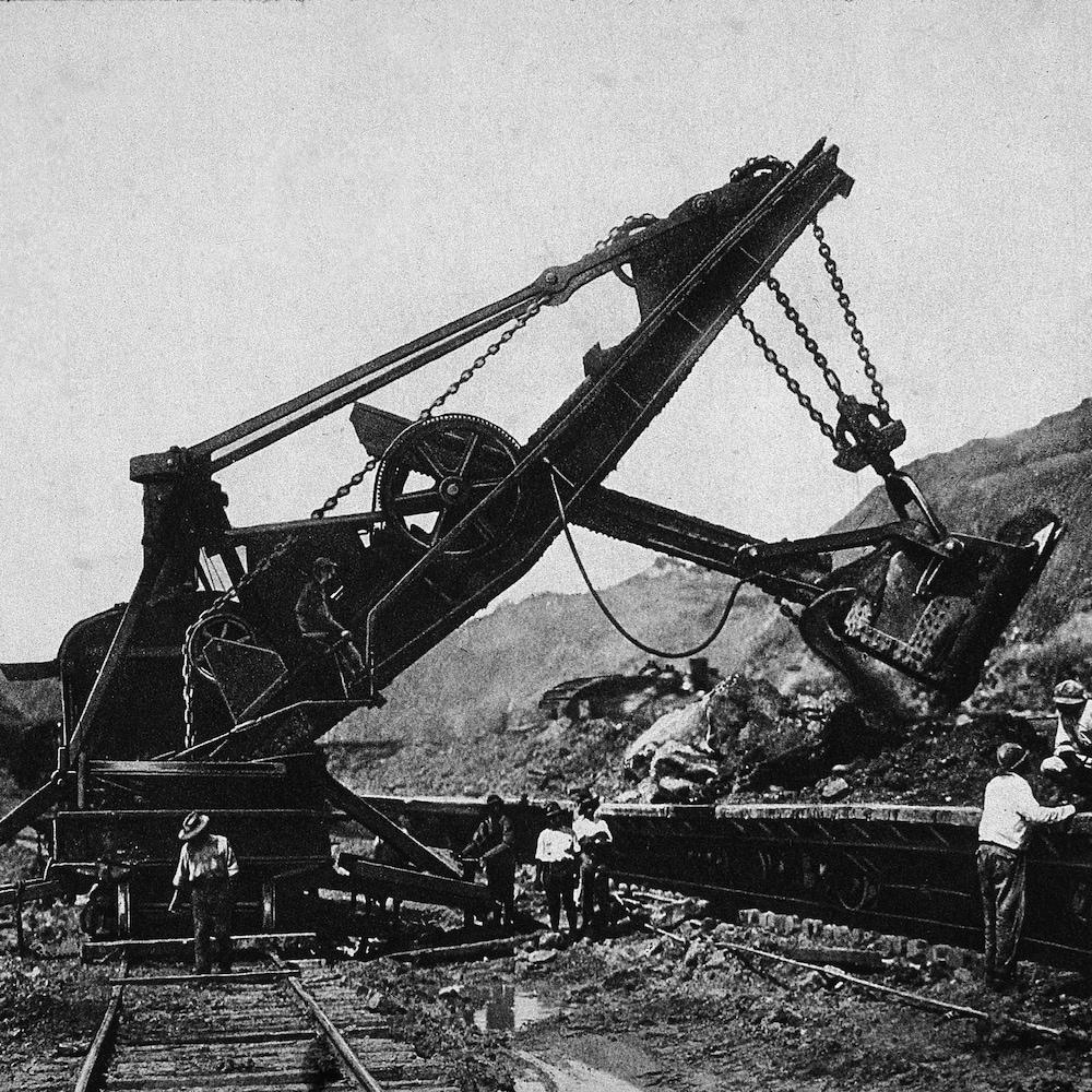 Photo en noir et blanc montrant une pelle mécanique creusant à côté d'une voie ferrée.