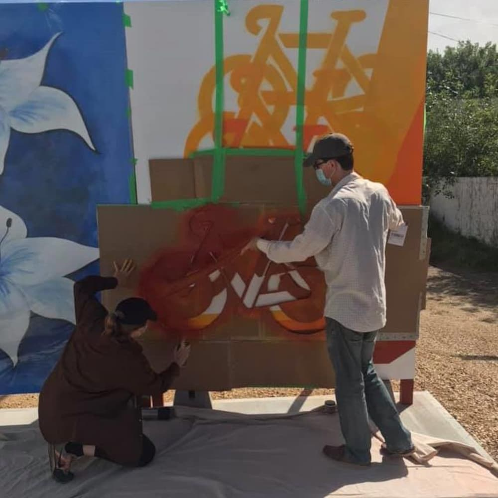 Deux artistes en train de peindre un tableau dans une oeuvre murale.