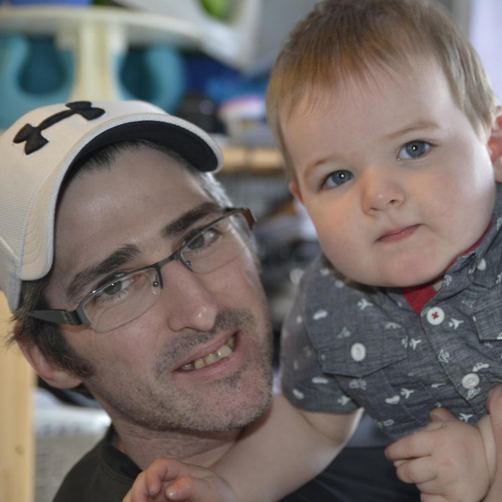 Un père tient son fils dans ses bras.