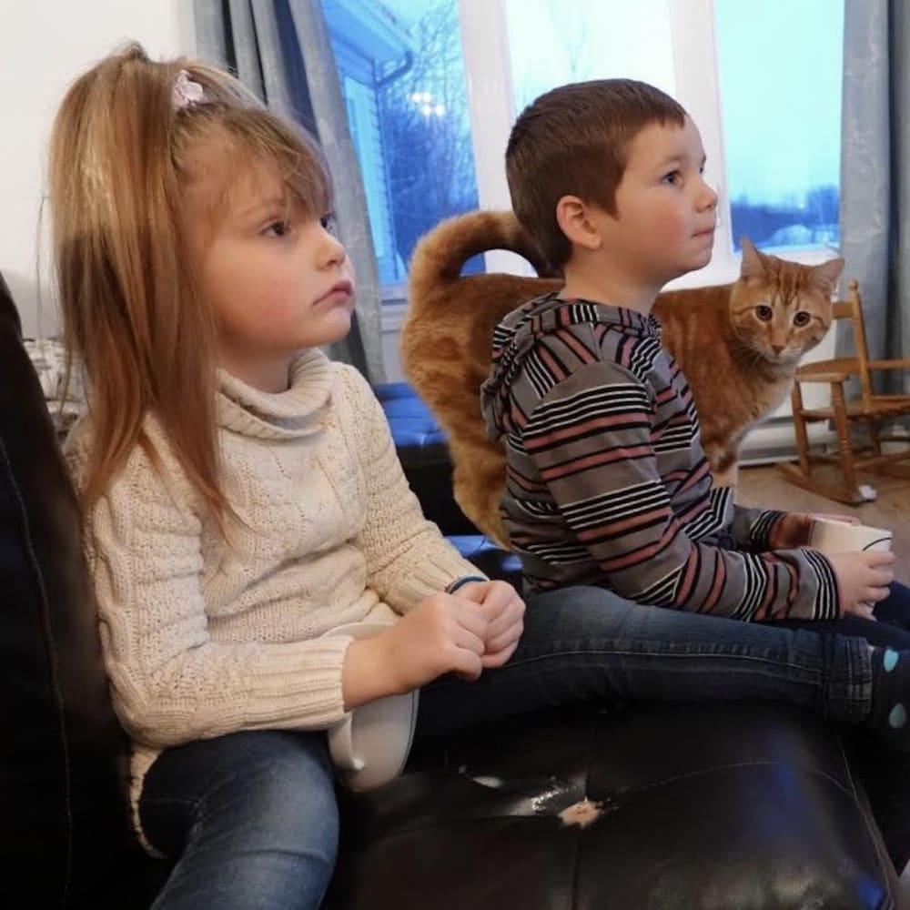 Deux enfants et un chat sont assis sur un divan.