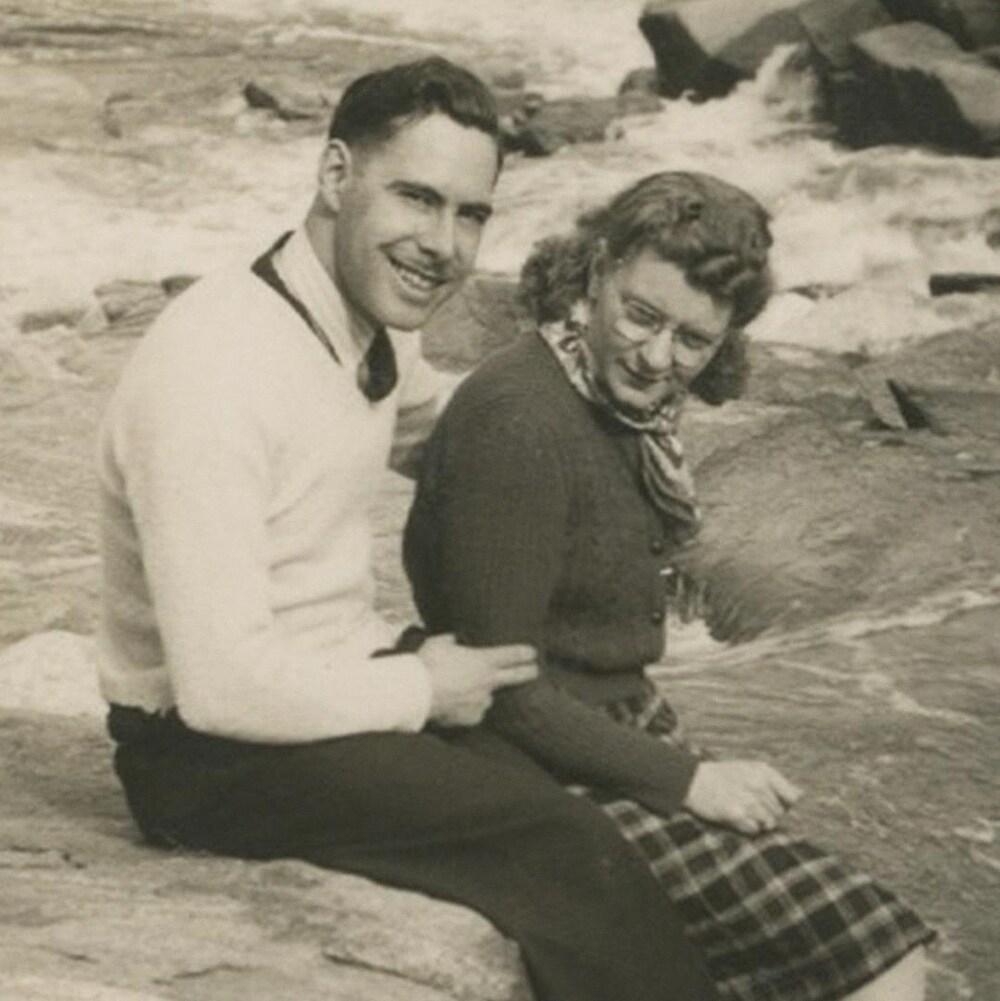 Antoine et Lauretta sont assis sur le bord de l'eau.