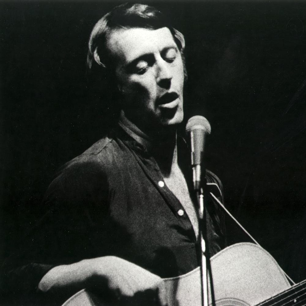 Marcel Aymar avec une guitare devant un micro.