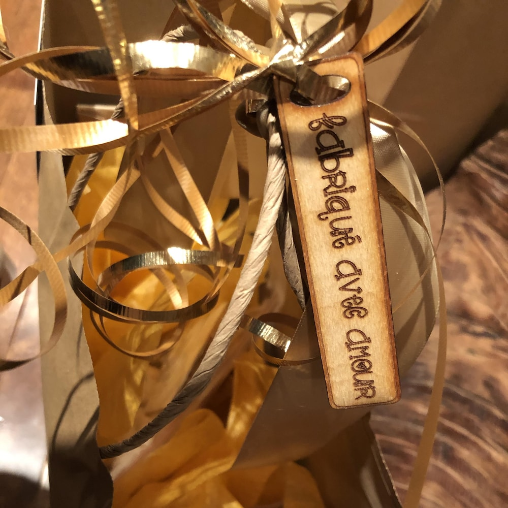 Un sac d'emballage et une étiquette en bois avec l'inscription : « Fabriqué avec amour ».