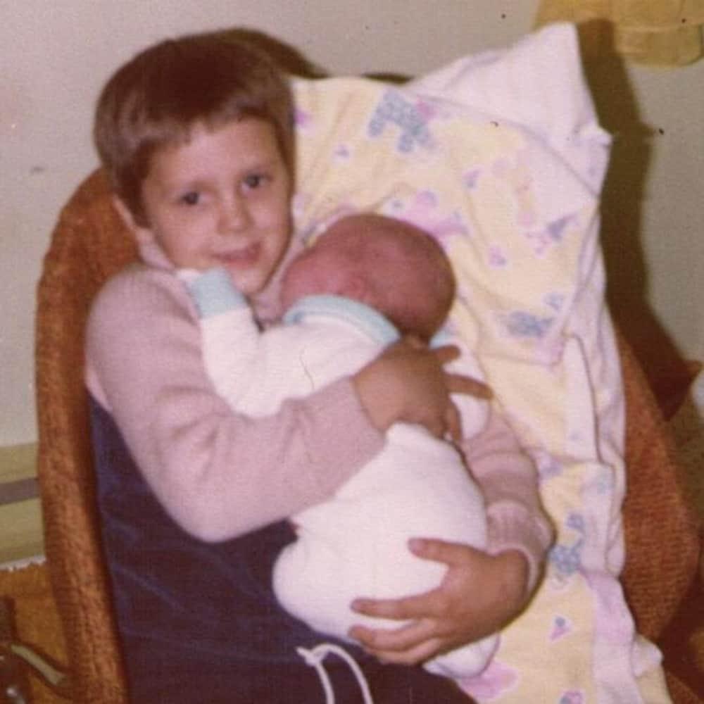 Stéphane, 6 ans, porte sa cousine Geneviève dans ses bras.