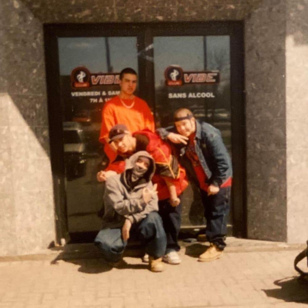 Quatre jeunes hommes devant la porte d'entrée d'un club.