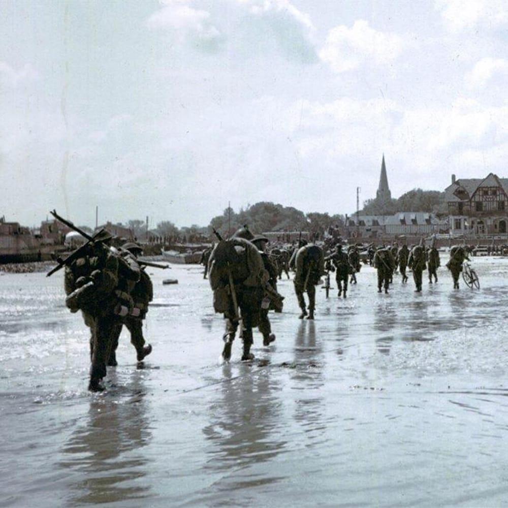 Les soldats marchent en fil indienne sur la plage avec leur équipement sur le dos.