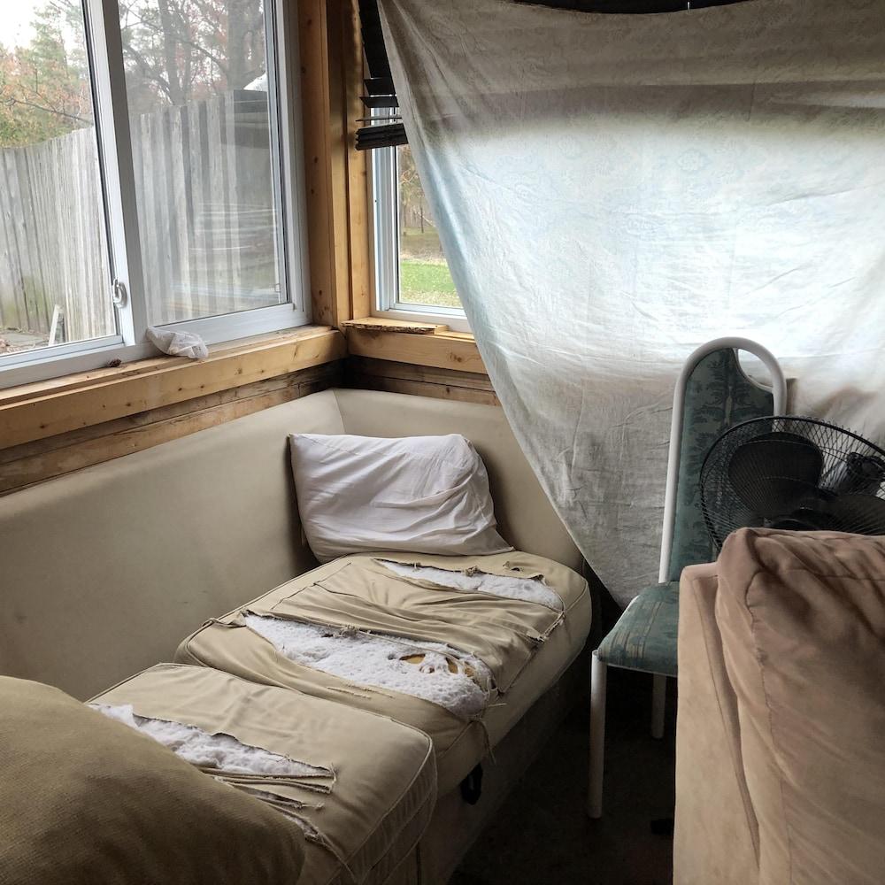 Un canapé déchiré à plusieurs endroits dans une petite pièce.