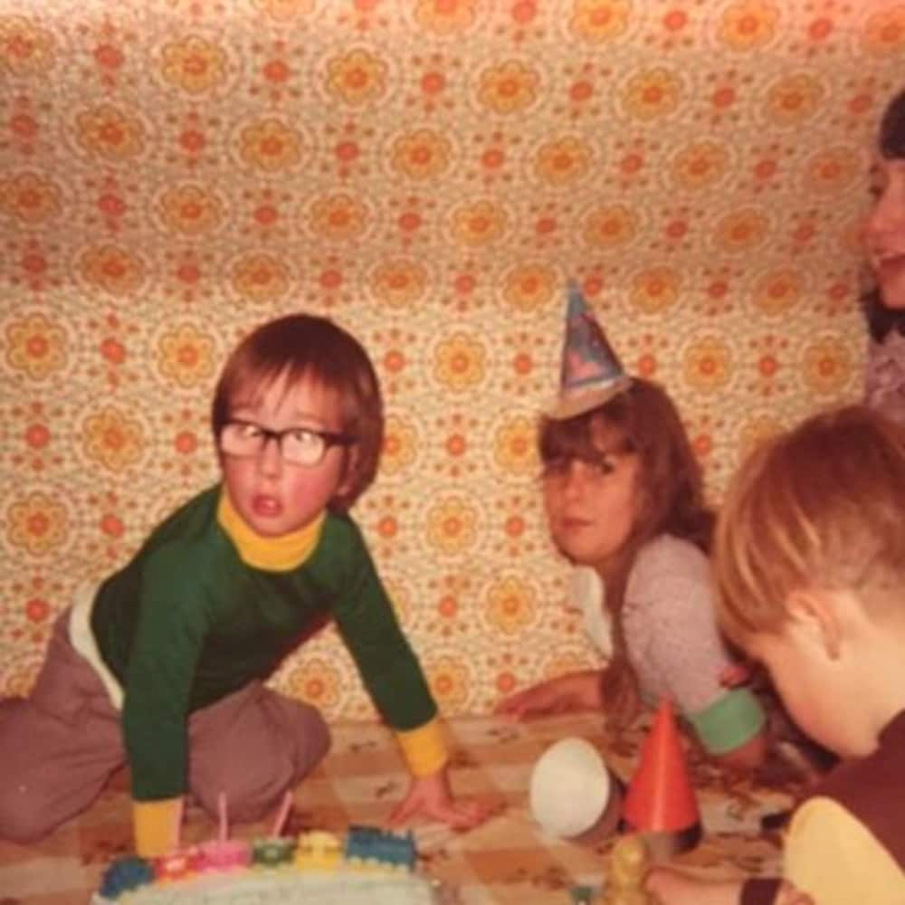 Tim Doucette, enfant, debout sur une table devant un gâteau d'anniversaire et entouré d'autres enfants.