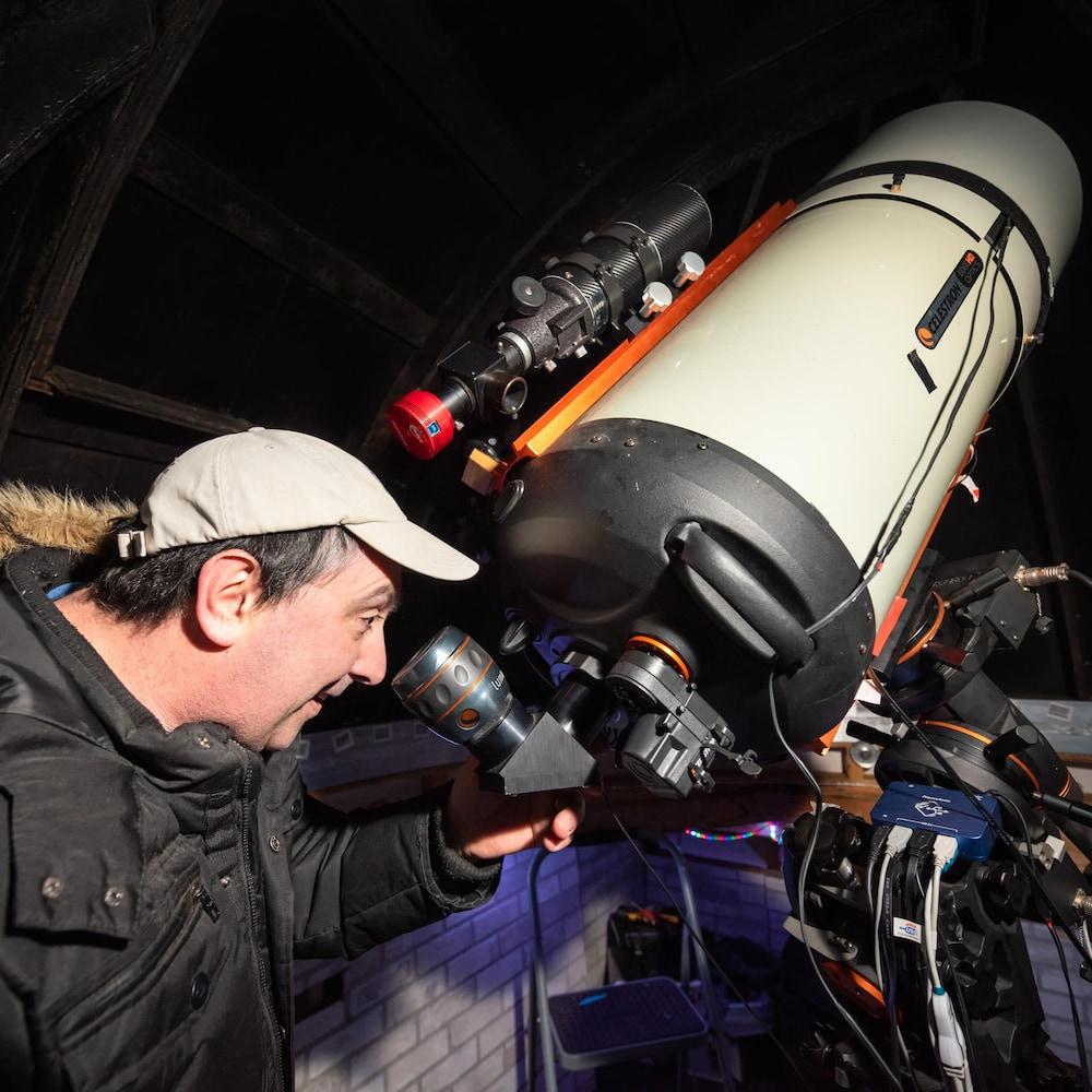 Tim Doucette regarde dans un gros télescope.
