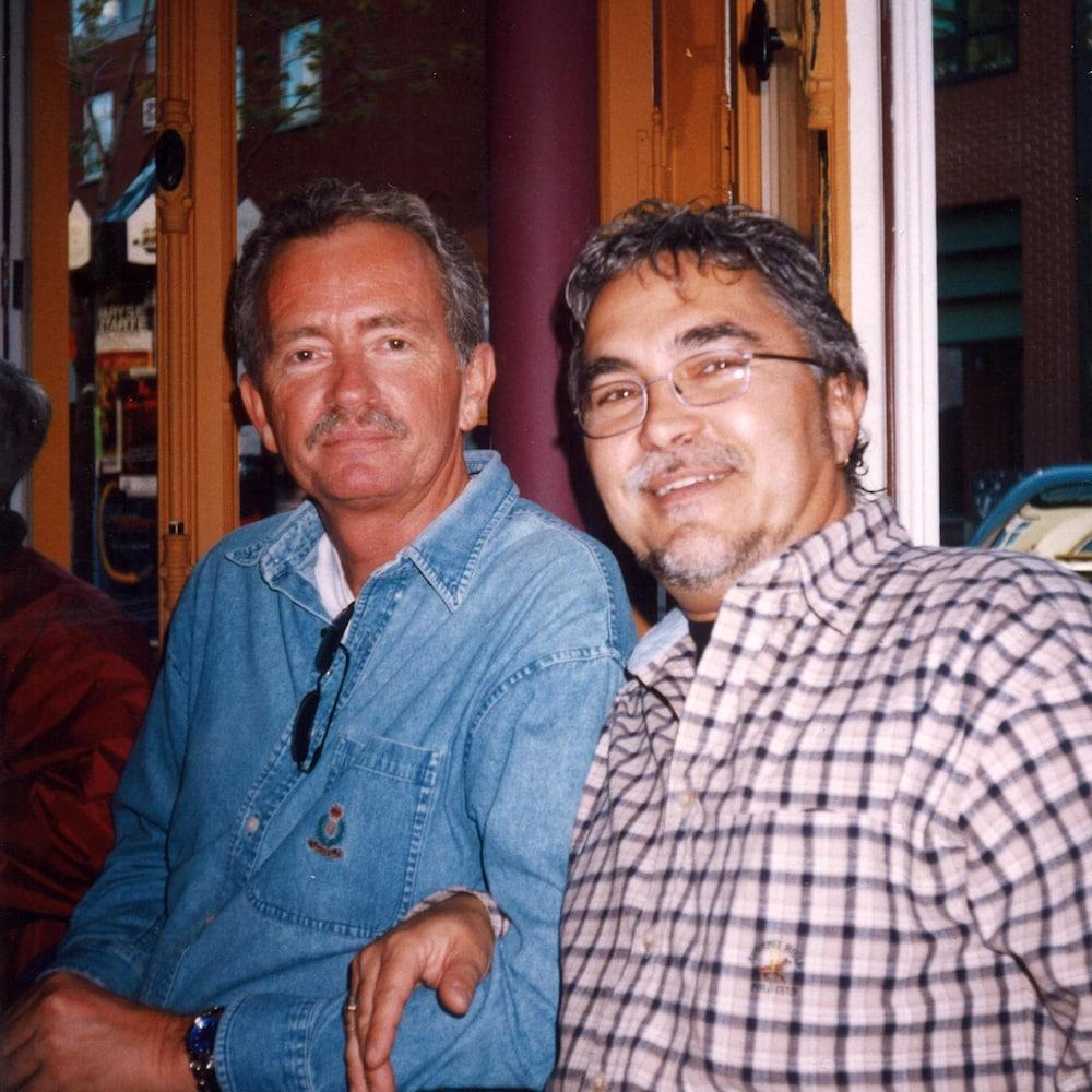 Deux hommes posent en souriant.