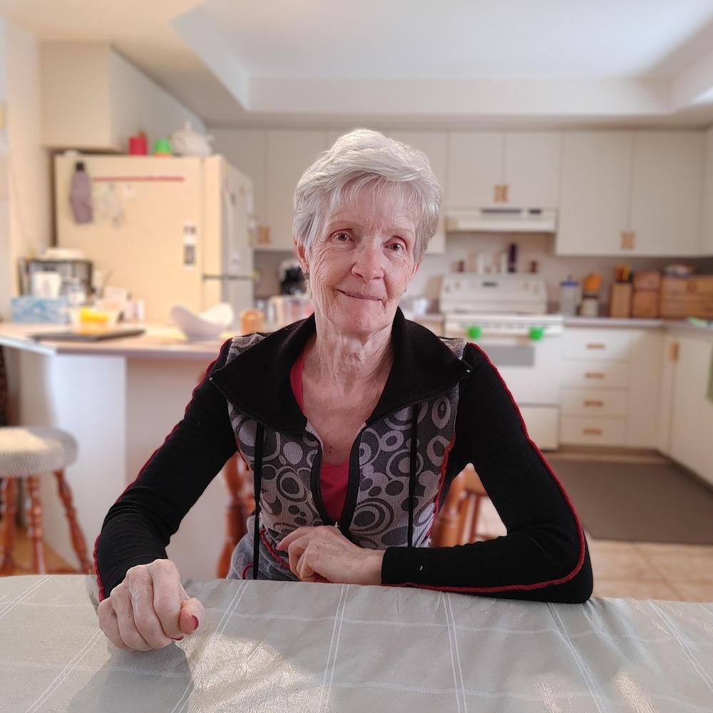 Une dame assise dans sa cuisine.
