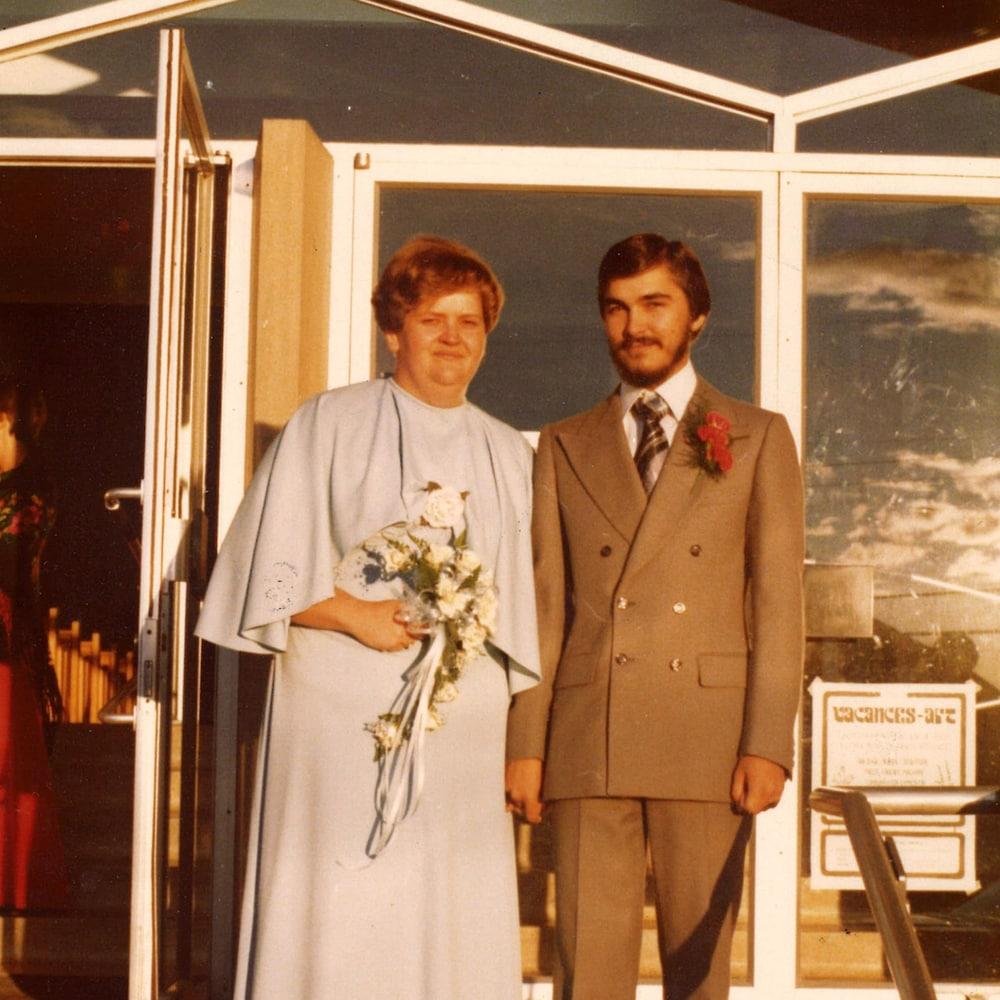 Un couple de mariés pose devant une église.