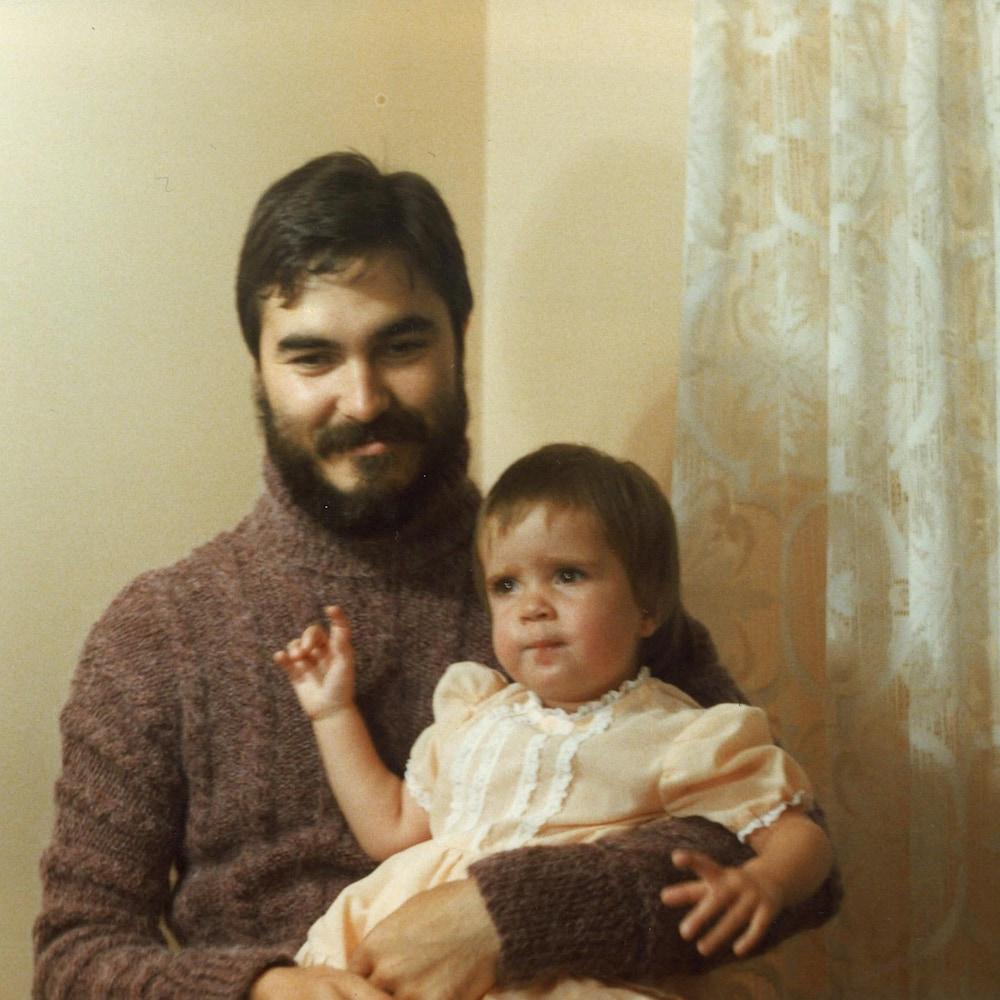 Un homme tient une petite fille dans ses bras.