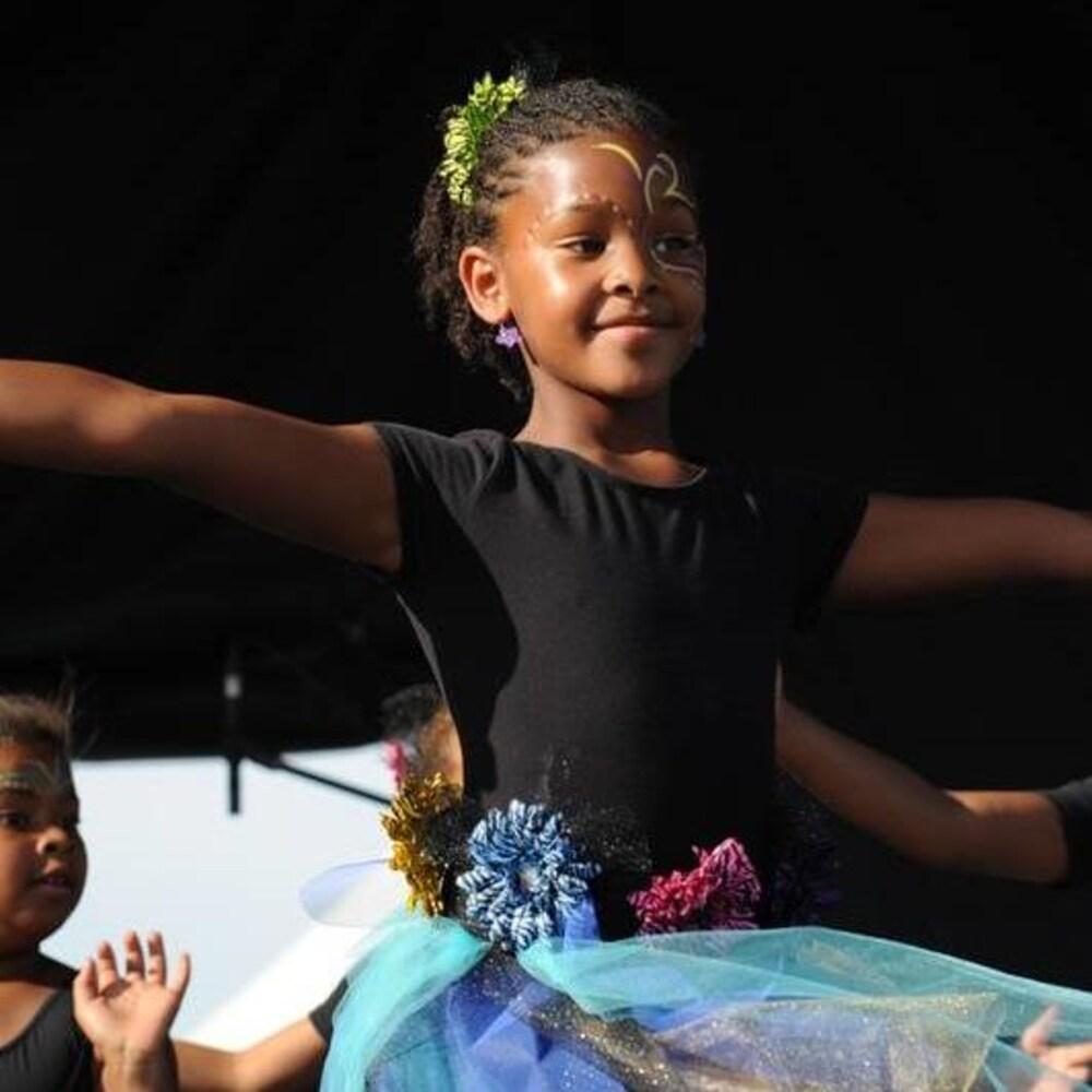 Une petite fille en train de danser vêtue d'une robe bleue.