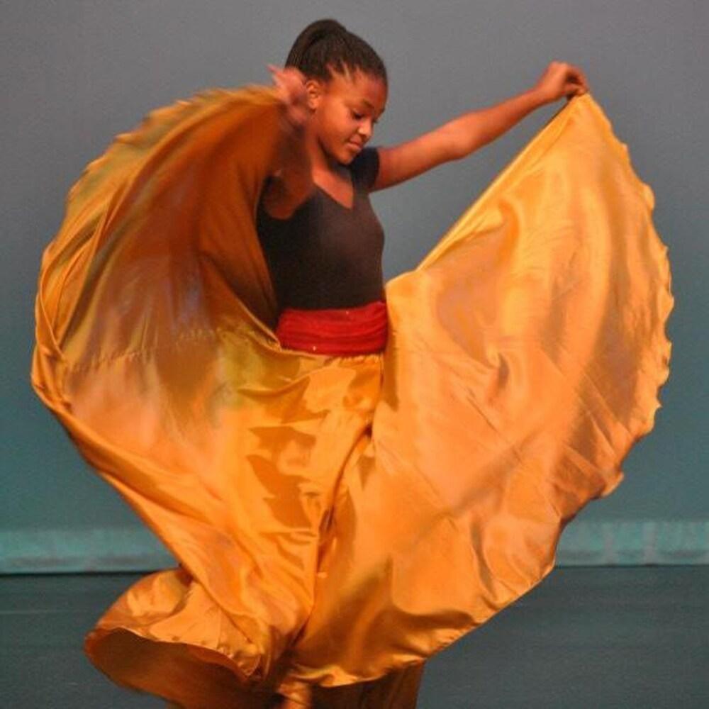Une fille qui danse avec un grande robe jaune.