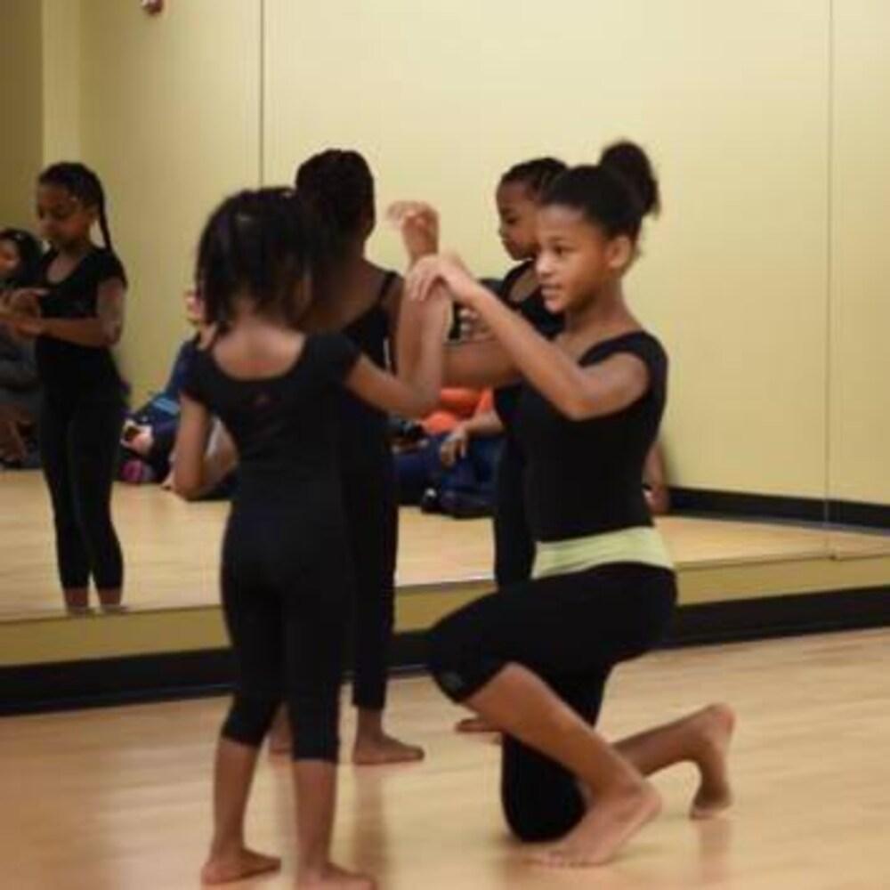 Une fille en train d'enseigner des mouvements de danse à une petite fille.