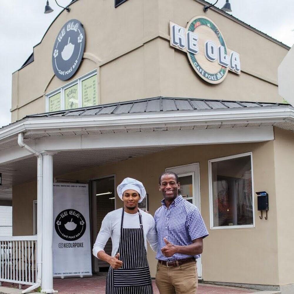 Les deux hommes sourient devant l'entrée du restaurant. Kevin-Koudbi porte un tablier et un chapeau de chef.