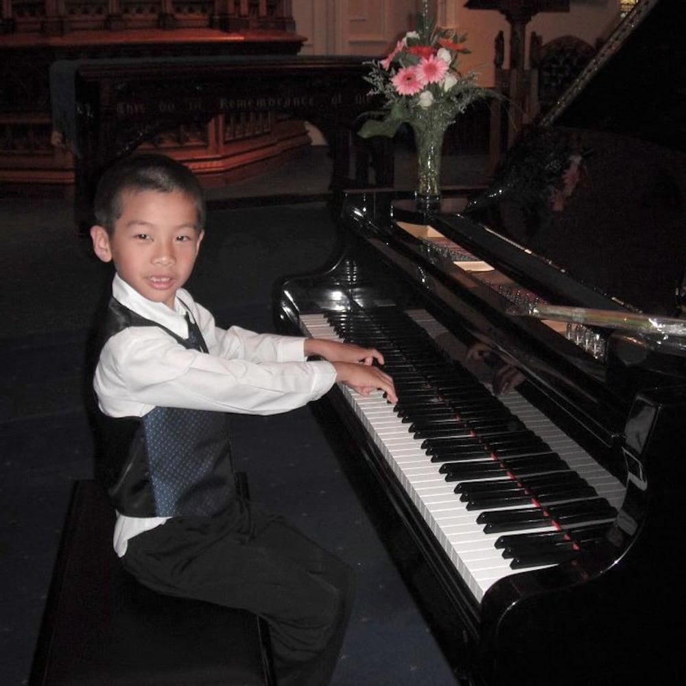 Un jeune garçon de six ans qui joue du piano.