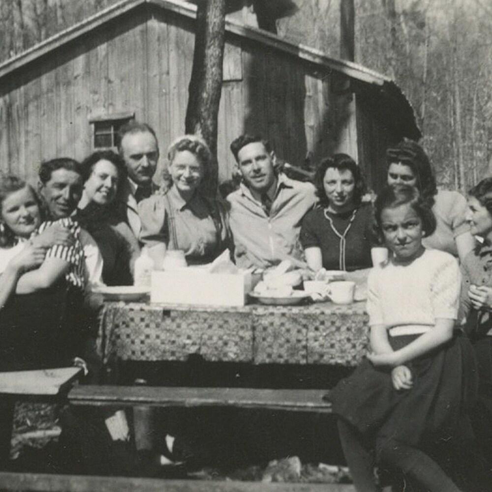 Antoine Trudel et Lauretta Gagnon sont assis autour d'une table avec des proches.