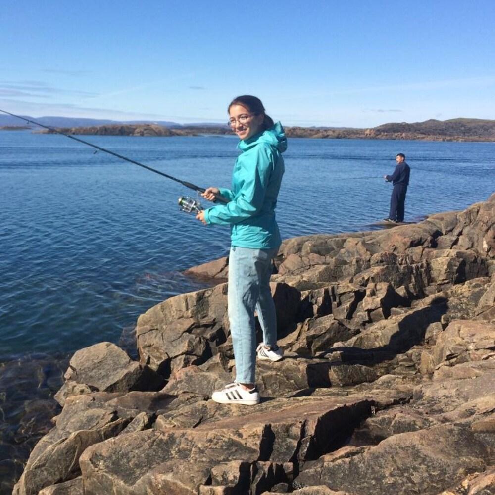 Une fille avec une canne à pêche debout sur un rocher au bord de l'eau.