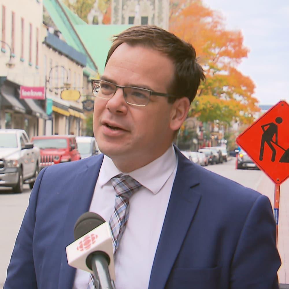 Patrick Taillon devant un micro de Radio-Canada sur le bord d'une rue.