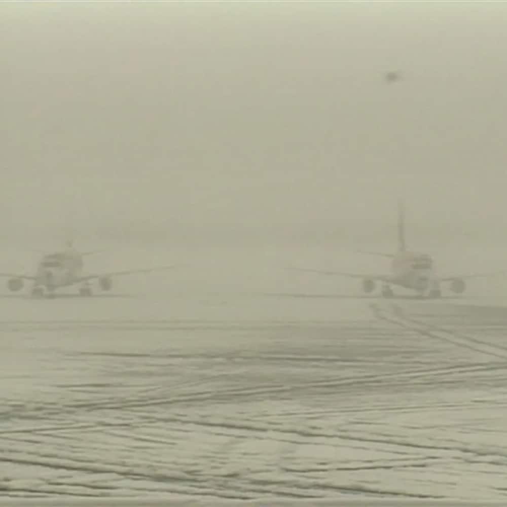 La visibilité quasi nulle sur le tarmac enneigé de l'aéroport.