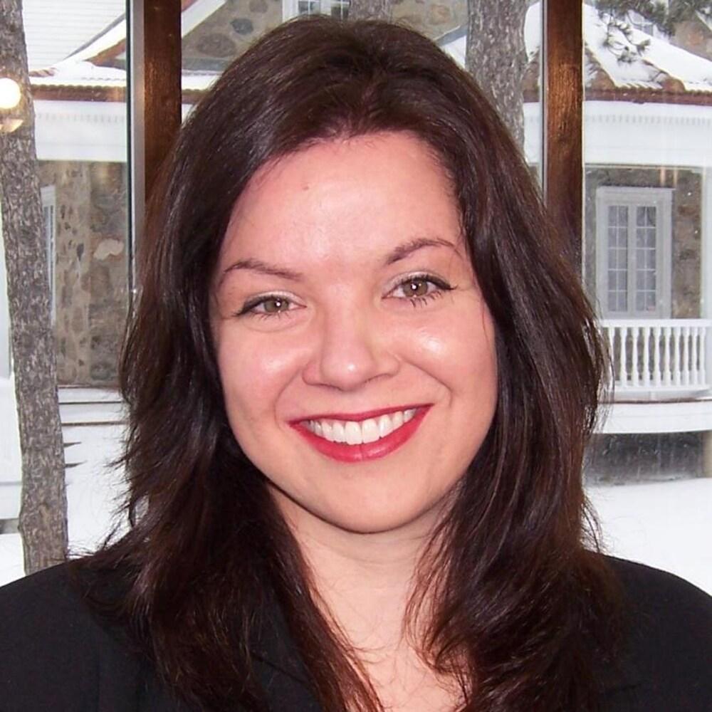 Une femme souriante devant un paysage hivernal.