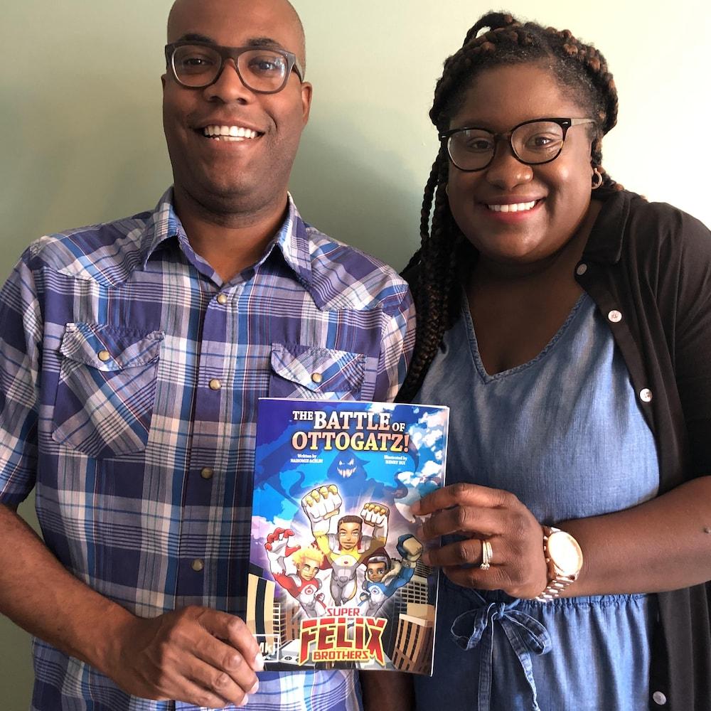 Un couple souriant tenant une bande dessinée.