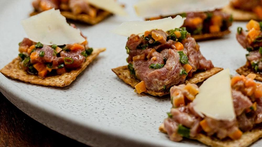 Des bouchées de tartare d'agneau aux carottes marinées, servies sur des craquelins maison.