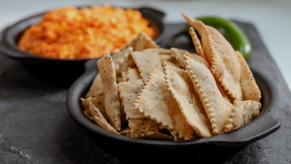 Des craquelins maison et un bol de trempette au fromage.