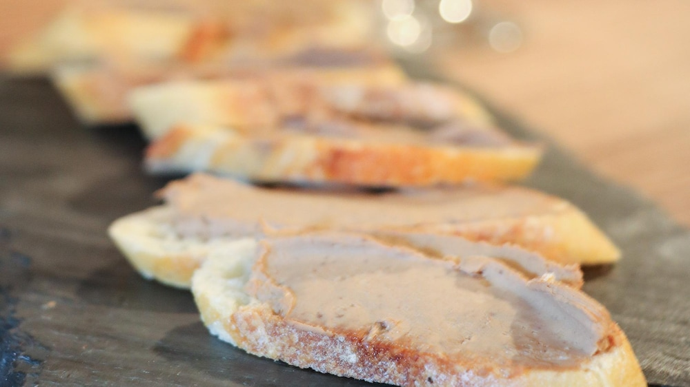 Des tranches de pain garnies de mousse de foie de volaille, déposées sur une ardoise.