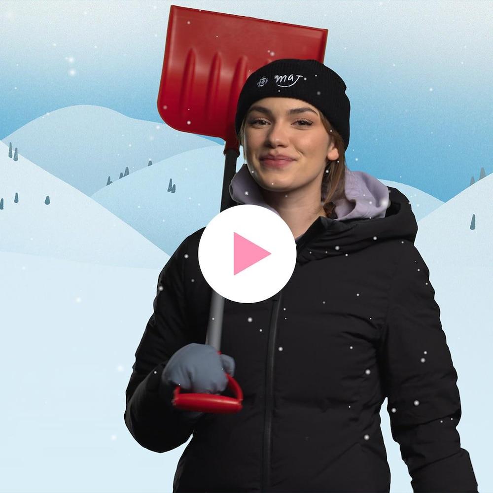 Livia Martin est habillée avec des vêtements d'hiver et tient une pelle dans sa main.