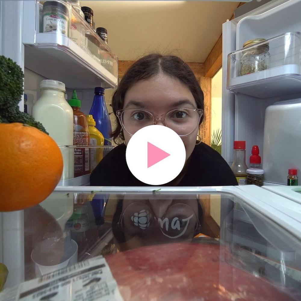 Dounia Ouirzane regarde à l'intérieur de son frigo.