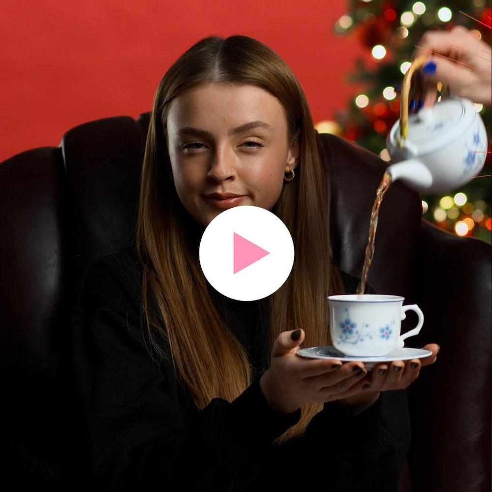 Alicia Moffet est assise confortablement dans une chaise et est entourée d'un sapin et de cadeaux de Noël.