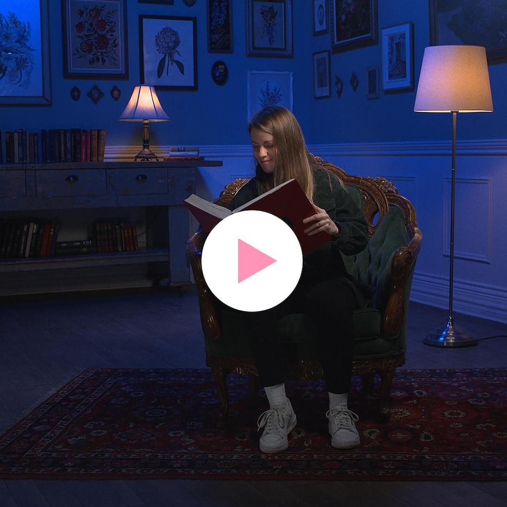 Judith Lussier, assise dans une chaise, lit un très gros livre.