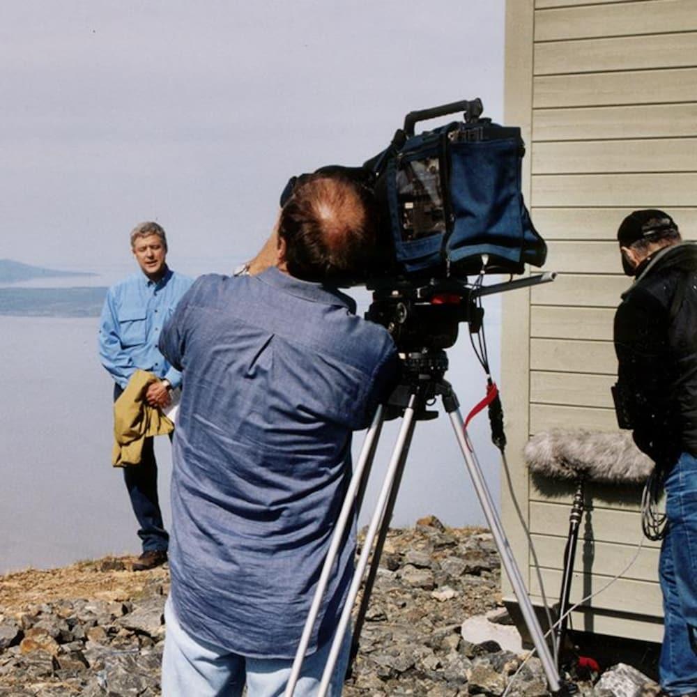 Tout en haut d'une colline, avec un point de vue magnifique sur un grand lac de l'est du Canada, un caméraman fait des tests de caméra avec Charles Tisseyre, qui, lui, est en arrière-plan.