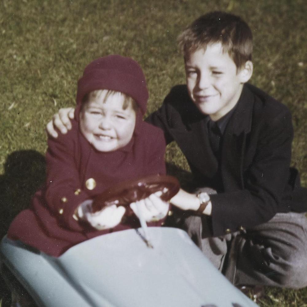 Assis sur le gazon, Charles Tisseyre enfant enlace tendrement son plus jeune frère François, qui, lui, se trouve dans une voiturette jouet.