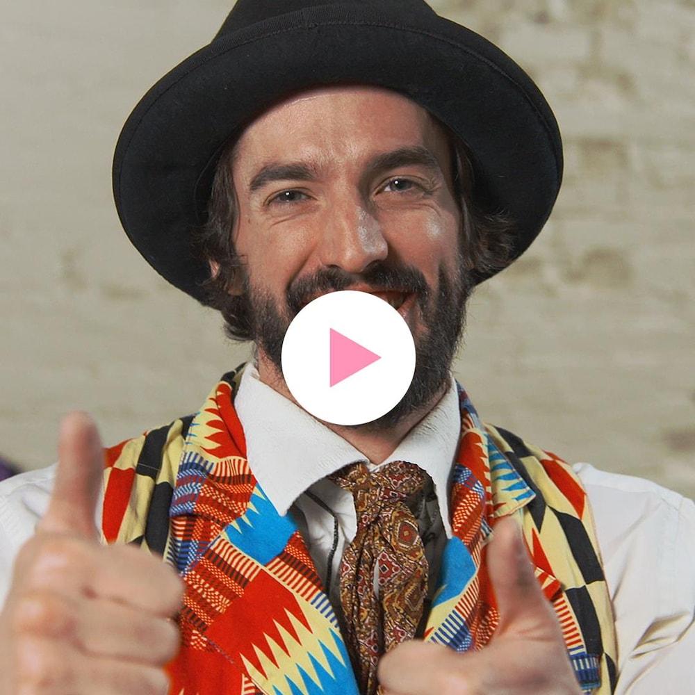 Guillaume Vermette, vêtu d'un chapeau et d'un veston coloré, lève les pouces vers le haut en souriant.