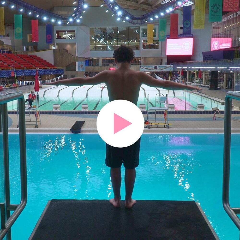 Iani, sur le tremplin de 10 mètres d'une piscine olympique, s'apprête à sauter.