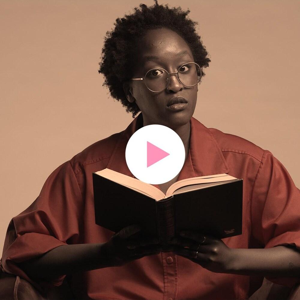 Leïla Donabelle Kaze est assise dans un fauteuil et tient un livre entre ses mains.
