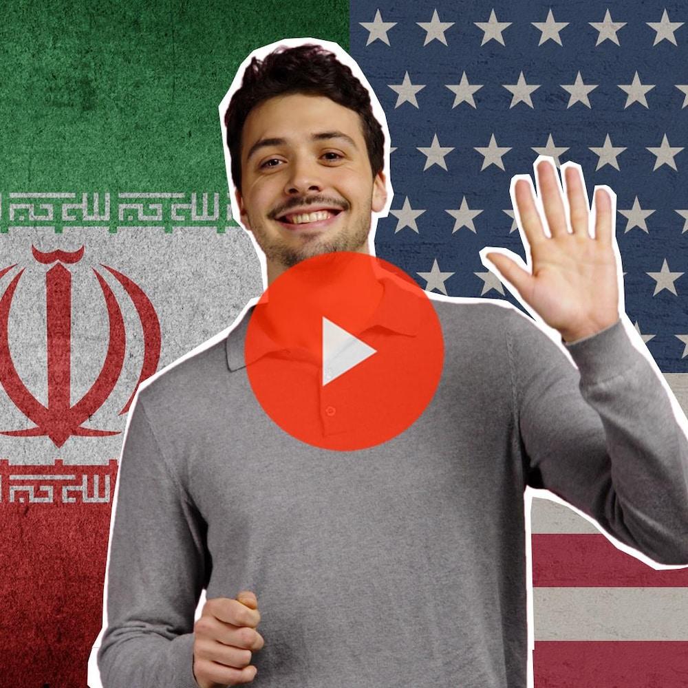 Thomas, devant les drapeaux iranien et américain, salue d'un air candide.