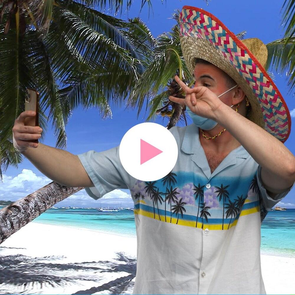 Massi Mahiou est en tenue de vacancier et prend un selfie avec son téléphone.