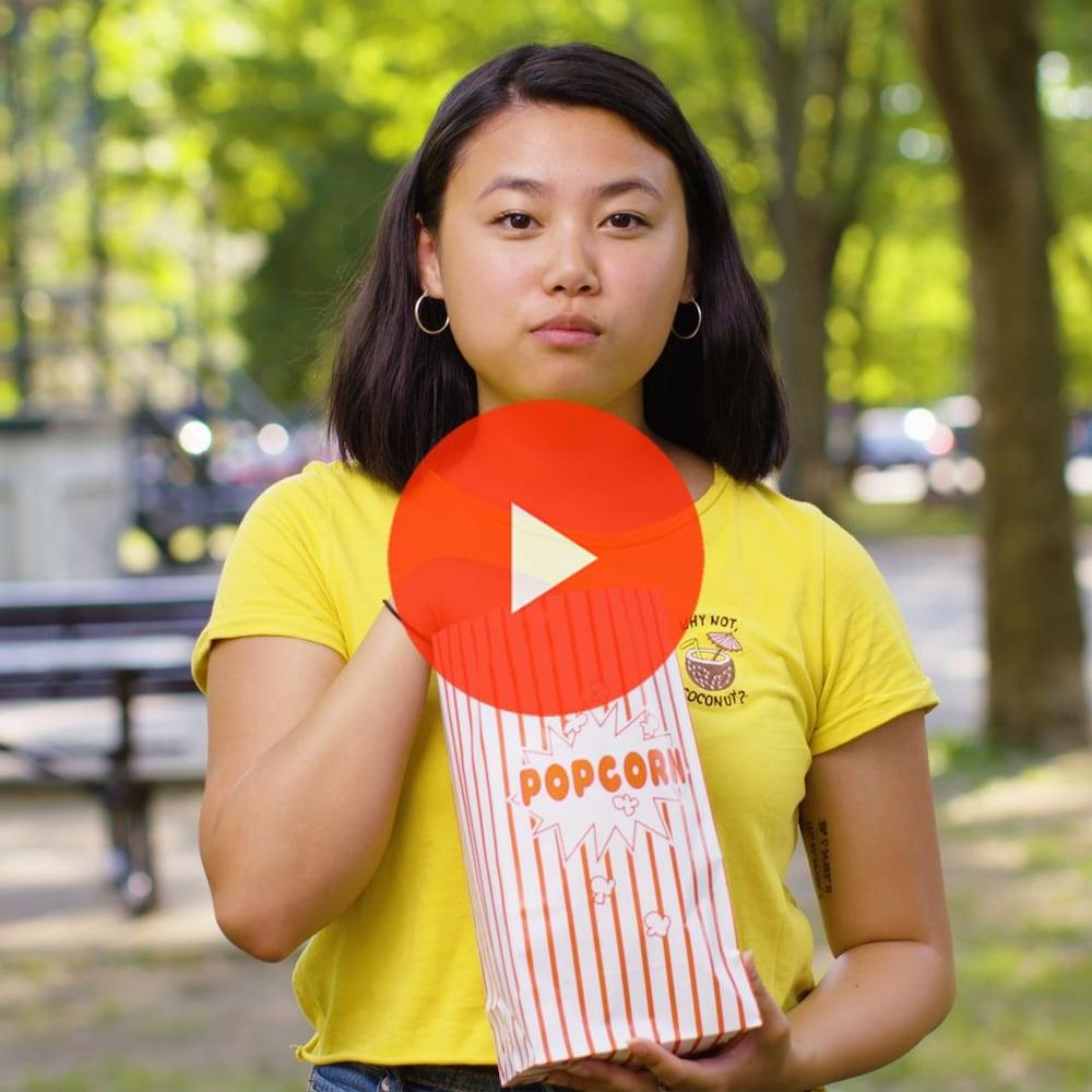Miniature de la vidéo. Anyjeanne Savaria regarde la caméra en mangeant du pop-corn.