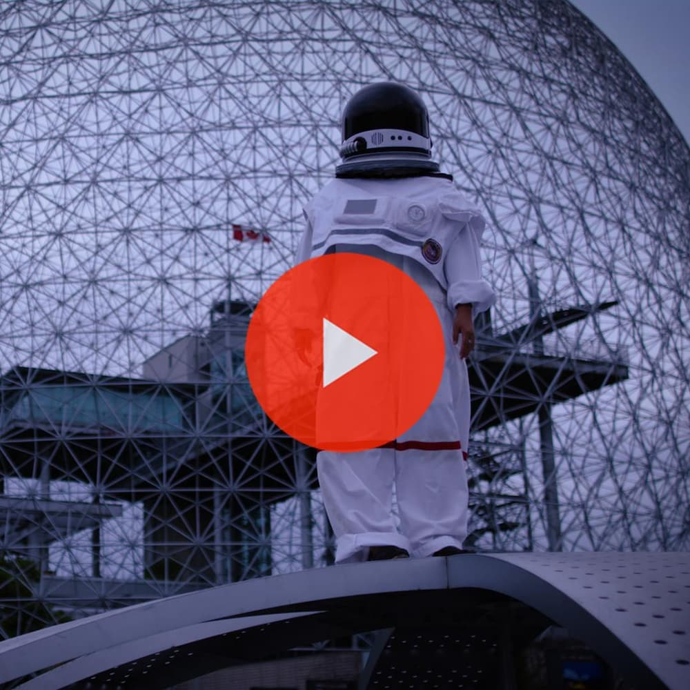 Miniature de la vidéo. Anyjeanne Savaria, vêtue en astronaute, se tient devant la biosphère de Montréal.