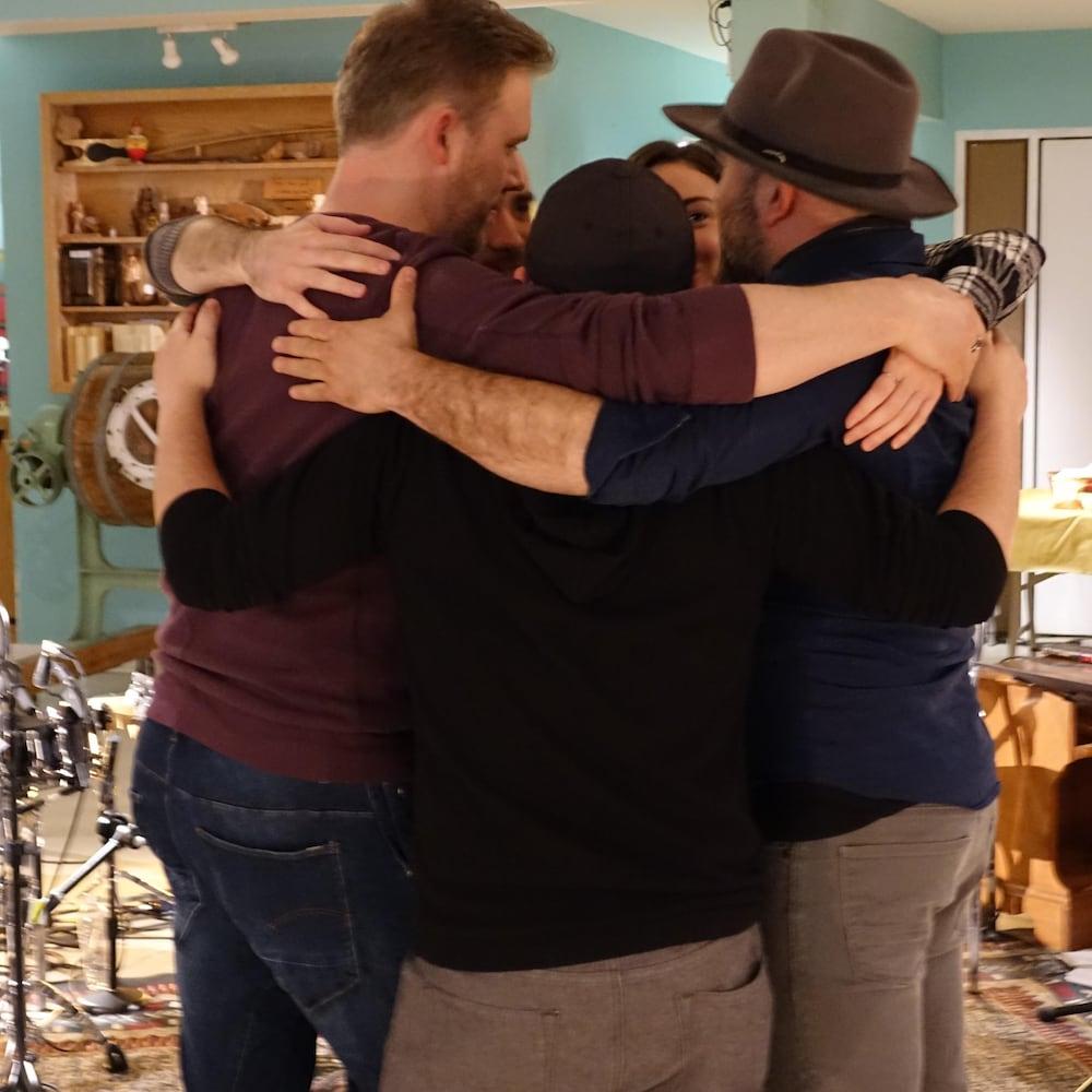 Câlin de groupe avant le spectacle de Kapuskasing en Ontario avec les artistes Brandon Girouard, Éléa Saunier et Raphaël Freynet, le directeur musical Éloi Painchaud et l'animateur et musicien Jean-François Breau.