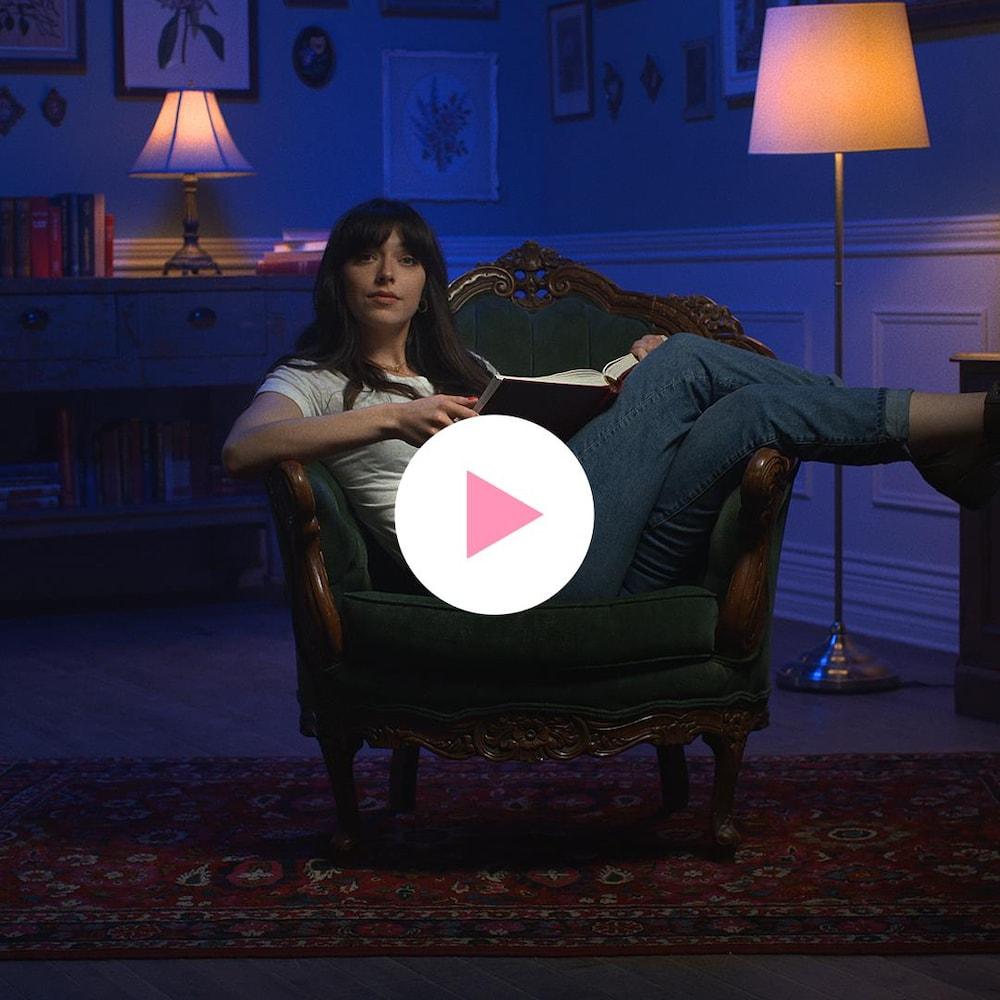 Rosalie Bonenfant est assise dans un fauteuil de façon détendue.