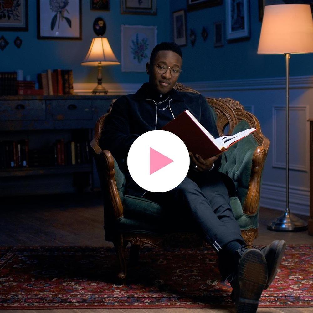 Nicolas Ouellet, assis confortablement dans un fauteuil, tient un grand livre entre ses mains et nous regarde.
