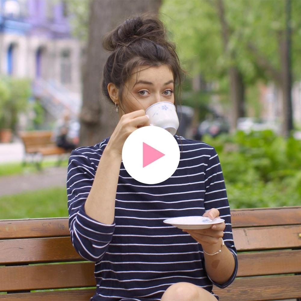 Rosalie Bonenfant, assise sur un banc de parc, boit le thé.