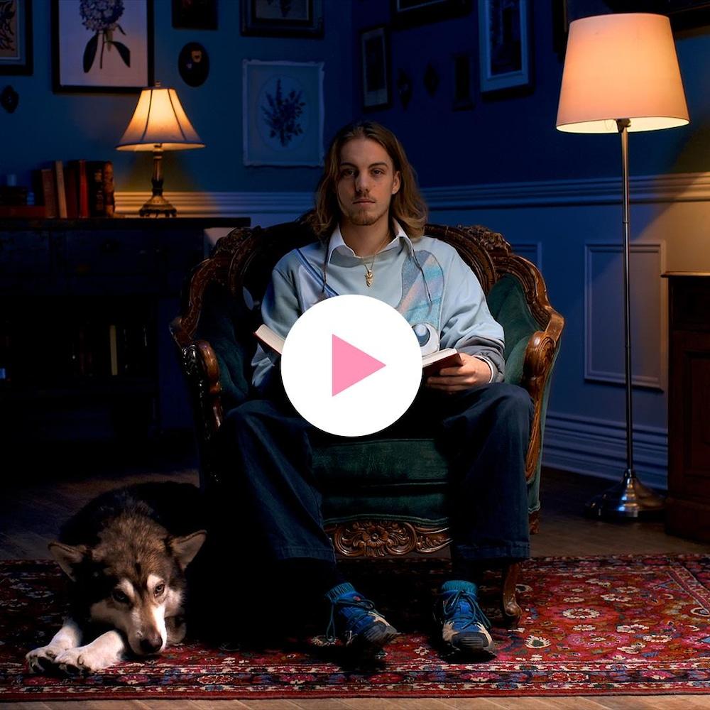 Antoine Desrochers est assis confortablement dans une chaise et tient un livre; son chien se tient à ses côtés.