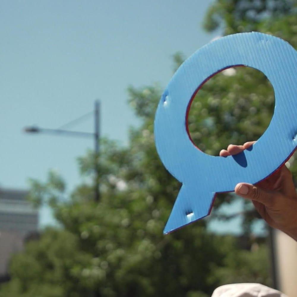 Le symbole Q de QAnon tenu dans une main.